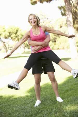 excercise: Senior Man Lifting Woman During excercise,fitness, In Park
