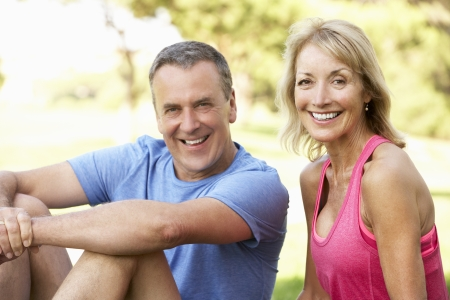 man looking out: Senior Couple Resting After Exercising In Park Stock Photo