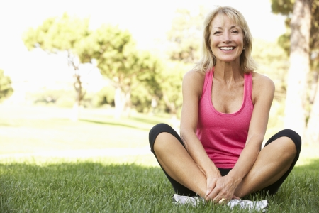excercise: Senior Woman Resting After Exercising In Park Stock Photo