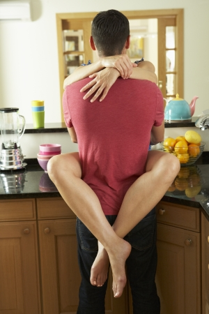 passionate embrace: Romantic Couple Hugging In Kitchen Stock Photo