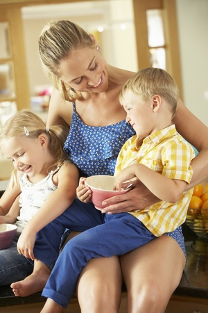 Mother And Children Having Breakfast Sitting On Kitchen Counter photo