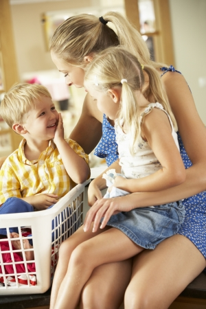 5 year old girl: Mother And Children Sorting Laundry Sitting On Kitchen Counter