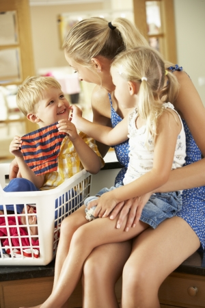 women in underwear: Mother And Children Sorting Laundry Sitting On Kitchen Counter