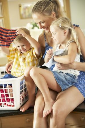 niñas en ropa interior: Madre y niños Ordenación Lavandería sienta en encimera de la cocina Foto de archivo