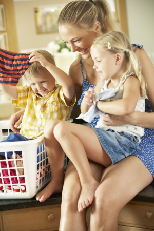 laundry: Mother And Children Sorting Laundry Sitting On Kitchen Counter