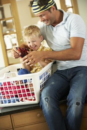 man laundry: Father And Son Sorting Laundry Sitting On Kitchen Counter Stock Photo