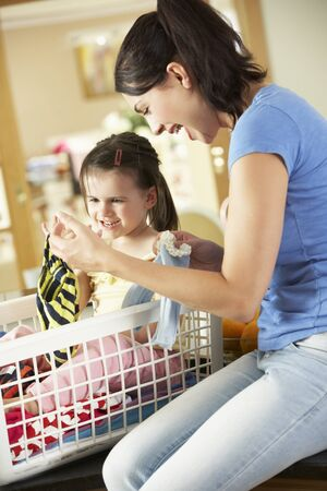 underpants: Mother And Daughter Sorting Laundry Sitting On Kitchen Counter