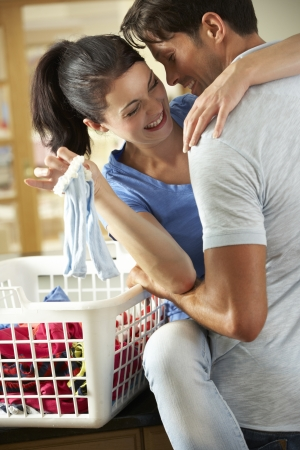 Romantic Couple Sorting Laundry In Kitchen photo