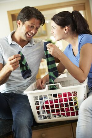 man laundry: Couple Sorting Laundry In Kitchen