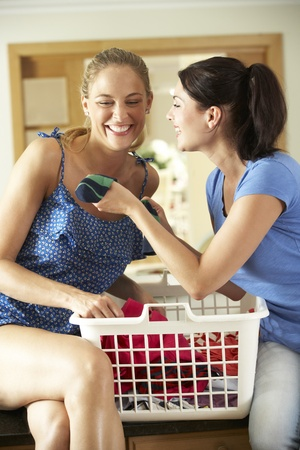 Two Women Sorting Laundry In Kitchen photo