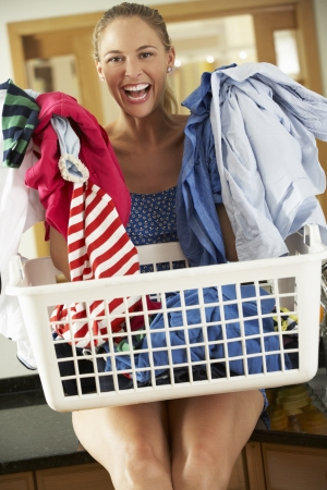 Woman Sitting On Kitchen Counter With Laundry Basket photo