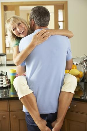 legs around: Romantic Senior Couple Hugging In Kitchen Stock Photo