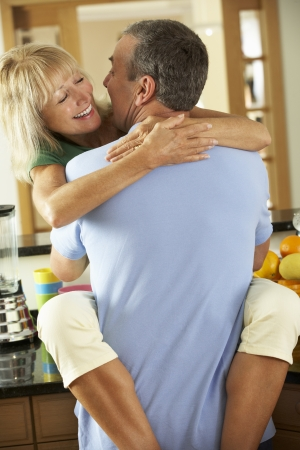 Romantic Senior Couple Hugging In Kitchen Stock Photo - 18723262