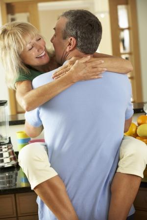 senior women: Romantic Senior Couple Hugging In Kitchen Stock Photo