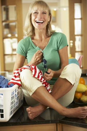 Senior Woman Sorting Laundry In Kitchen photo