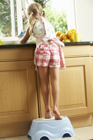 the stool: Girl Standing On Plastic Step In Kitchen Helping With Washing Up