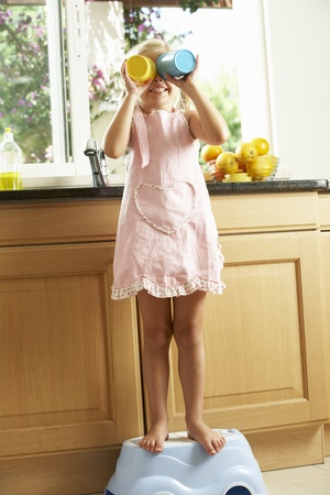 5 year old girl: Girl Standing On Plastic Step In Kitchen Helping With Washing Up