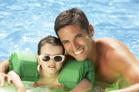 Father And Daughter With Armbands In Swimming Pool photo