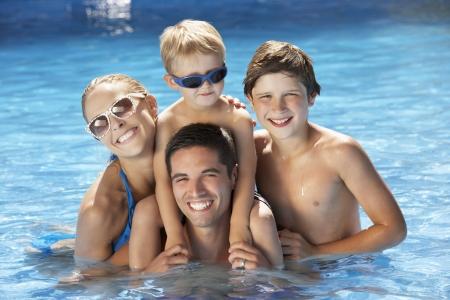 ni�os nadando: Familia que se divierte en piscina Foto de archivo