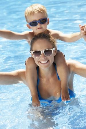 splash pool: Madre e hijo se divierten en piscina Foto de archivo