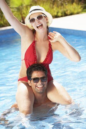 mid adult woman: Couple Having Fun In Swimming Pool