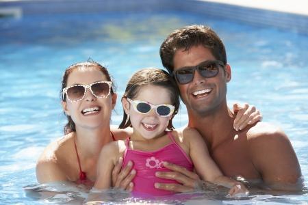 splash pool: Family Having Fun In Swimming Pool Stock Photo
