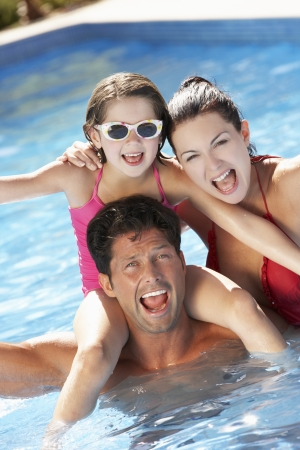active holiday: Family Having Fun In Swimming Pool Stock Photo