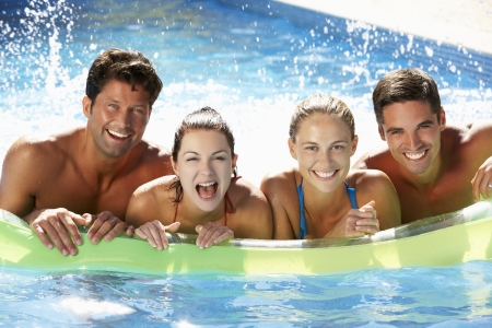 floating: Group Of Friends Having Fun In Swimming Pool