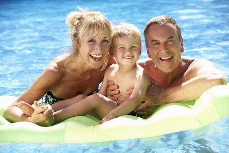 abuelos: Los abuelos y el nieto que se divierten en piscina Foto de archivo