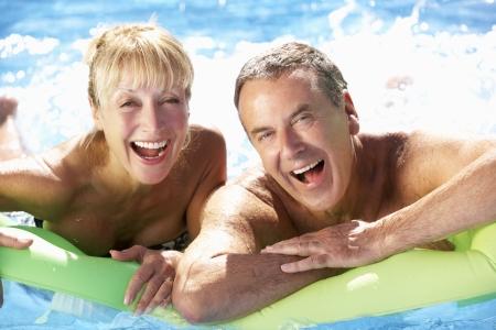 hombres haciendo ejercicio: Pares mayores que se divierten en piscina