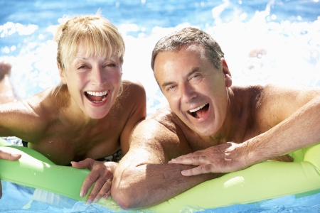couple exercising: Senior Couple Having Fun In Swimming Pool