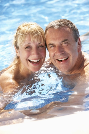 splash pool: Senior Couple Having Fun In Swimming Pool