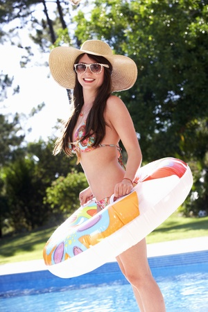 Woman Standing By Pool With Inflatable Ring photo