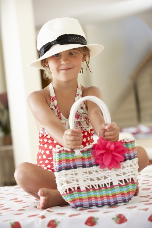 swimming costume: Girl Wearing Swimming Costume With Straw Hat And Bag
