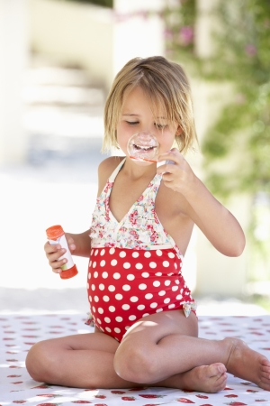swimming costume: Girl Wearing Swimming Costume Blowing Bubbles