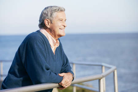 blue sky thinking: Senior Man Looking Over Railing At Sea
