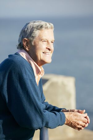 Senior Man Looking Over Railing At Sea photo