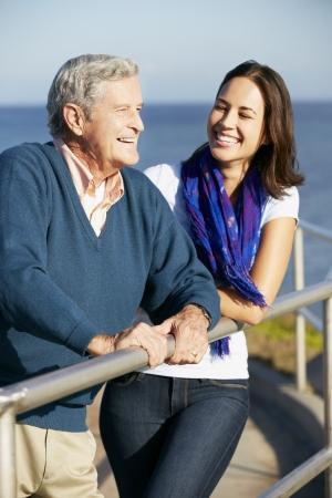 80s adult: Hombre mayor con hija adulta que mira sobre Barandilla en el mar