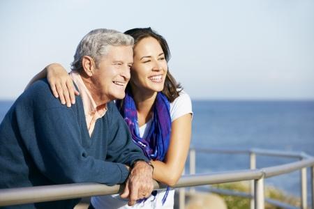 padre e hija: Hombre mayor con hija adulta que mira sobre Barandilla en el mar