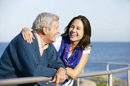 mid adult: Senior Man With Adult Daughter Looking Over Railing At Sea Stock Photo