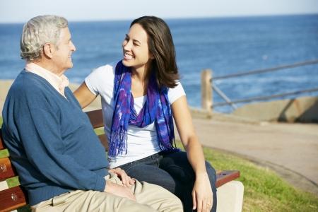 pere et fille: Senior homme assis sur le banc avec le descendant adulte par mer