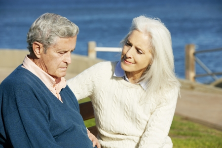 Senior Woman Comforting Depressed Husband Sitting On Bench Stock Photo