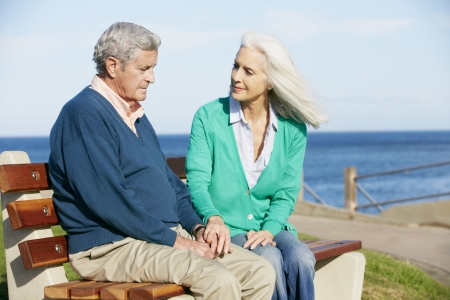 carer: Senior Woman Comforting Depressed Husband Sitting On Bench Stock Photo