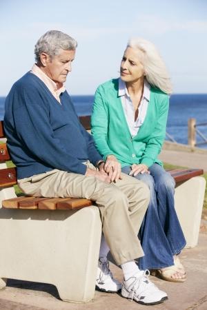 80s adult: Mujer mayor que conforta esposo deprimido se sienta en banco