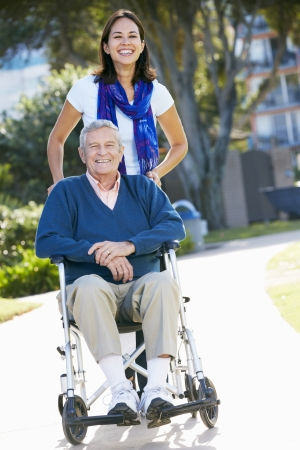 disable: Adult Daughter Pushing Senior Father In Wheelchair Stock Photo