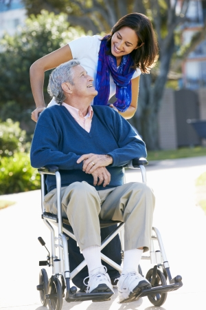 wheelchair man: Adult Daughter Pushing Senior Father In Wheelchair Stock Photo