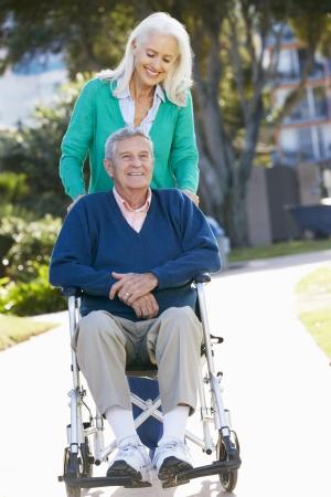 80s adult: Mujer mayor empuje marido en silla de ruedas Foto de archivo