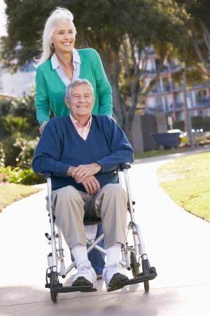 Senior Woman Pushing Husband In Wheelchair photo