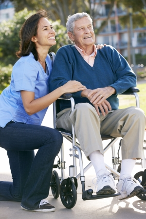 carer: Carer Pushing Senior Man In Wheelchair Stock Photo