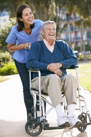 sillas de ruedas: Carer Empujar hombre mayor en silla de ruedas Foto de archivo